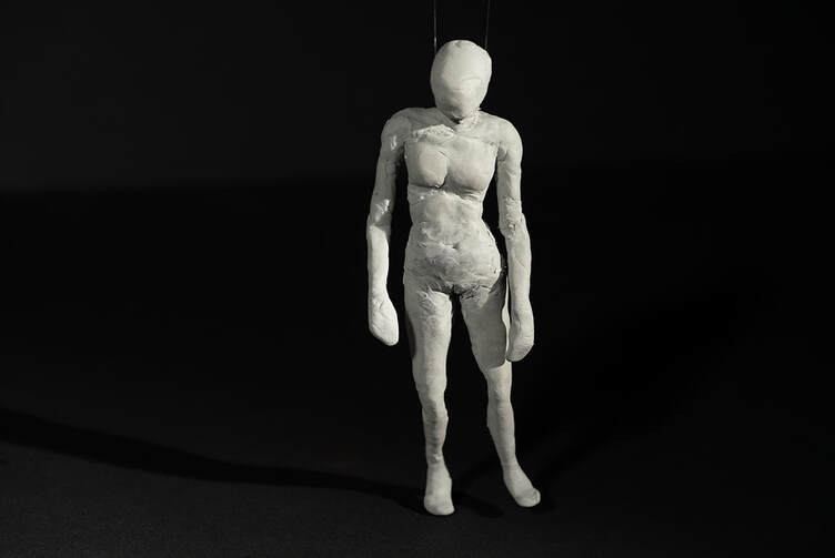 A rough clay sculpture of a female body being suspended by fishing line on a black background.