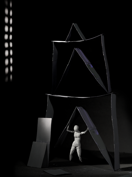 A piece of photographic art depicting a rough, clay female figure holding up a house of cards. Giving a feeling of endurance and strength.The house is painted with black and a touches of purple. The scene is black with shadows in the background and 2 long rows of bright lights on the left side. There are 2 black cards leaning against the house like construction is still underway.