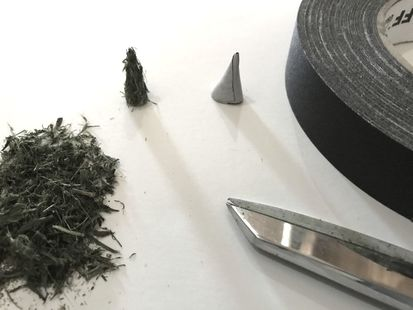 A small pile of dried grass with a role of black gaffers tape and scissors. Showing miniature pine trees are being created.