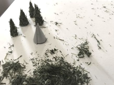 A pile of dried grass with tiny cones made of reversed tape. Handmade miniature pine trees are shown in the background.