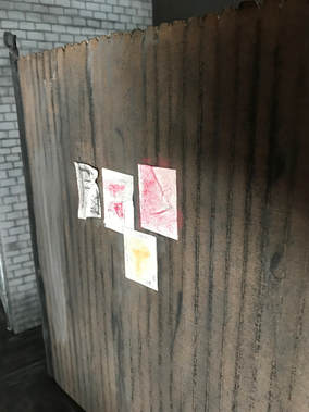A miniature brown, wood fence made of cardboard. It has flyers posted on it and is in front of a gray brick wall also made of cardboard.