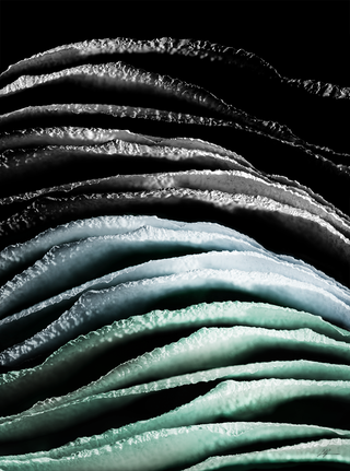 A scene with green, blue and black. Textured ridges flow from the front to back. The back ridges seem to be dying off.