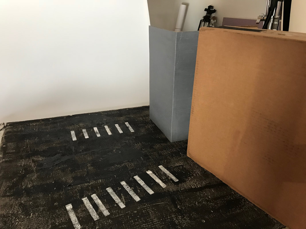 A roughly painted black surface also painted with white crosswalk stripes. Cardboard is used to make miniature buildings.