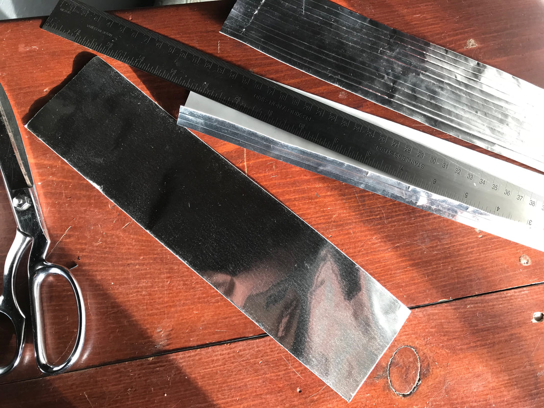 Pieces of metal tape being creased over a metal ruler to create many thin folds. Shown on a wooden table with scissors.