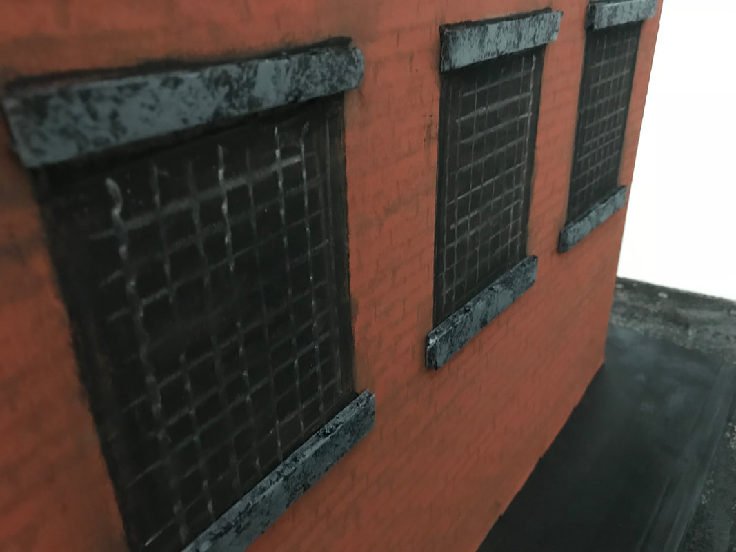 A close up of handmade, miniature barred windows in a brick building.