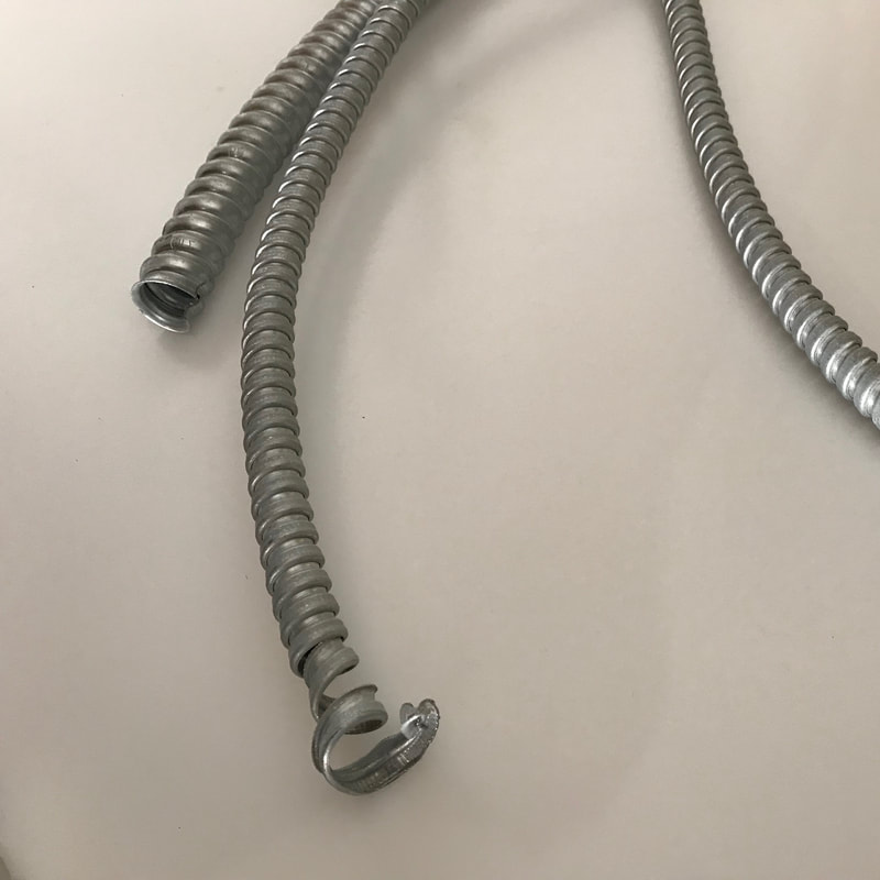 Three pieces of electrical, metal conduit lying on a white surface.